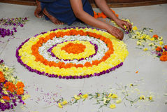 Flower decoration. A girl decorating the floor with different colors of flowers for a wedding function Stock Image