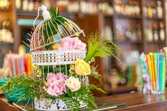 Flower decoration. With pink hydrangea and yellow roses, different green leaves and white miniature bird cage Stock Photos