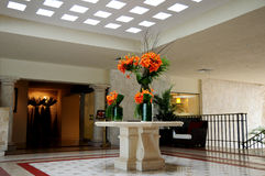 Flower decorations in lobby. A view of a large flower bouquet or display in the center of a spacious hotel or building lobby Royalty Free Stock Images