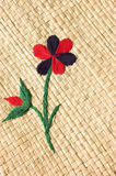 Flower embroidery on basket. Basket weave pattern of a straw like natural material with simple flower plant sewn on top Royalty Free Stock Image