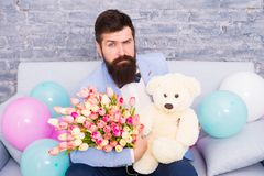The flower experts. Spring gift. Bearded man hipster with flowers. Bearded man with tulip bouquet. March 8. Love date stock photography