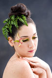 Flower eye makeup. Beautiful brunette face with pink green yellow eye flower petal makeup, isolated on gray stock image