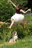 Flower Fairy. A young girl leaps over her little dog while playing in the garden on a warm summer day Royalty Free Stock Image