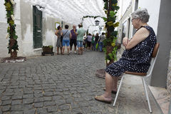 Flower festival in Campo Maior, Portugal. CAMPO MAIOR, PORTUGAL -23 AUGUST 2015: Flower festival in Campo Maior. A woman is sitting beside her house at decorared Royalty Free Stock Photography