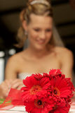 Flower Focus. A bride in background with a bouquet of flowers Stock Image