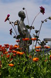 Flower garden. A flower garden in full bloom with a statue of a women in the background Stock Photo