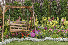 Flower garden. Wooden swing seat in flower garden Stock Images