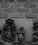 Flower gentleman by the blazon. Shot in black and white detail on the sculpture on the facade of this historic building representing some characters. Set in Stock Image