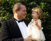 Flower girl. Man and little girl in formal wear in outdoor setting stock images