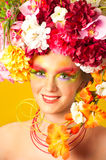 Flower Girl. Beautiful young girl wearing flower wreath. Creative makeup with long feather artificial eyelashes and bright colorful eyeshadow royalty free stock photography