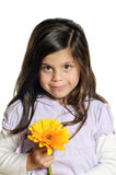 Flower girl. A little girl holding a flower in front of her face with a cheerful look Royalty Free Stock Photography