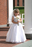 Flower girl. Wearing the bridal veil holding a bouquet of flowers royalty free stock images