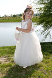 Flower Girl. Young flower girl standing next to a pond Royalty Free Stock Photo