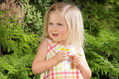 Flower Girl. Little blond girl holding wildflowers with a nervous look on her face Royalty Free Stock Image