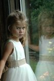 Flower Girl. Looking at the camera by the window Stock Images