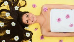 Flower Girl. Beautiful brunette Girl with colourful flowers lying on a towel Stock Image