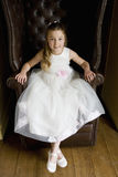 Flower girl (10-12) in armchair, smiling, portrait, elevated view Royalty Free Stock Photo