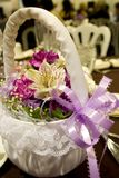 Flower girl basket with purple ribbon. Spring flowers in a white cloth basket with lavender ribbon at a wedding royalty free stock photos