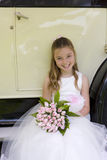 Flower girl (10-12) with bouquet of flowers sitting by vintage car, smiling, portrait, elevated view Royalty Free Stock Photography