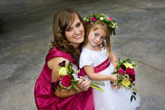 Flower Girl and Bridesmaid. A bridesmaid and a flower girl smiling together at a wedding reception royalty free stock photos
