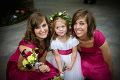 Flower Girl and Bridesmaids. Two bridesmaids and a flower girl smiling together at a wedding reception royalty free stock photography