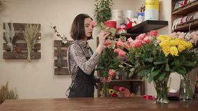 Flower girl is choosing freshest roses and creating floral composition in studio. Young salesperson woman is working in a floral workshop. She is getting it out stock video footage