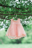 Flower girl dress. Hangs from tree outside styled wedding stock image