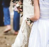 Flower girl holding brides wedding dress stock photos