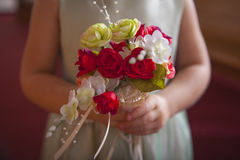 Flower Girl Holding Flowers. Flowers being held by young flower girl Stock Photos