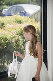 Flower girl looking in a window. Flower girl with flower basket looking throw window Stock Photo