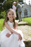 Flower girl (10-12) on path by church, smiling, portrait Stock Photos