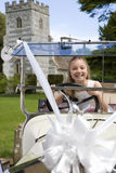 Flower girl (10-12) pretending to drive vintage car, tower in background, smiling, portrait Royalty Free Stock Photo