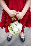 Flower Girl in a Red Dress. Holding a hanging white bouquet Stock Photo