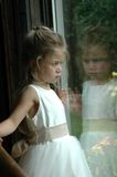 Flower Girl Reflection. Flower girl looking out the window at garden flowers after the ceremony Royalty Free Stock Images