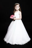 Flower girl with roses. Cute girl with roses and in flower-girl dress - studio portrait on black background, old finish Royalty Free Stock Image