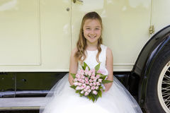 Flower girl (10-12) sitting on side of vintage car, smiling, portrait Royalty Free Stock Photography