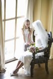Flower girl (10-12) smiling at bride in chair, elevated view (lens flare) Royalty Free Stock Photography
