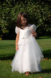 Flower Girl on Tip Toes. Four year old girl in a white formal dress.  She has bare feet and walking in the grass Stock Photo