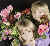 Flower Girls. Twins nestled in bouquet of flowers Royalty Free Stock Images