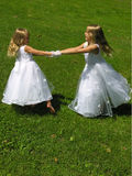Flower girls spinning. Two young girls spin around together in their flower girl dresses Stock Photos