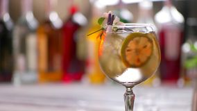 Flower on glass with cocktail. Glass of beverage rotates slowly. Tom collins decorated by flower. Feel the taste of summer stock video