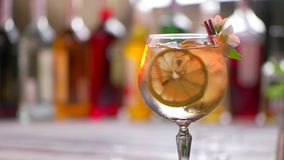 Flower on glass with drink. Glass with beverage is rotating. Simple decorated cocktail. Tom collins served at club stock footage