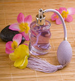 Flower and glass perfume bottle. Purple flower and glass perfume bottle on the wood mat stock photos