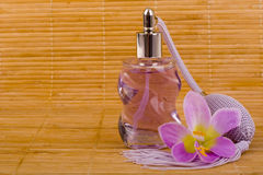 Flower and glass perfume bottle. Purple flower and glass perfume bottle on the wood mat stock photography