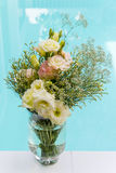 Flower glass vase and bouquet of pink and yellow flower with blu Royalty Free Stock Photography