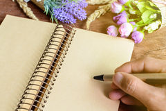 Flower and hand writing on blank notebook on wooden table. Flower and hand writing on blank notebook on old wooden table Royalty Free Stock Photography
