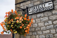 Flower Hanging Basket with road sign, Stokesley or Scarborough Royalty Free Stock Photos