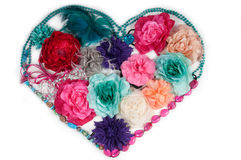 Flower heart made of ladies accessories. Heart formed from artificial flowers (woman barretts) and beads isolated on white Stock Photo