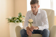 Flower for her. Confident young men sitting at the chair and hol Stock Photos