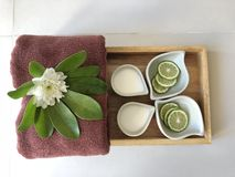Relaxing at spa. Flower and herb serving in wooden plate with towel in spa royalty free stock photos